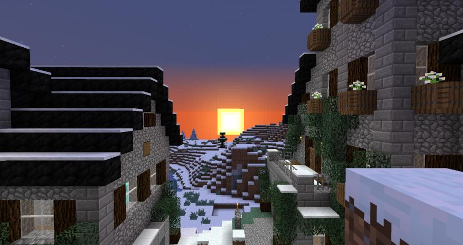 Sale el sol entre unos edificios en la nieve